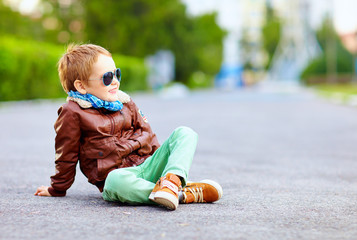 stylish boy in leather jacket posing on the ground