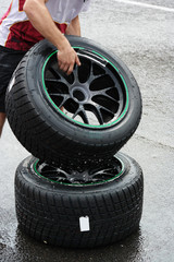 Mechanic takes a wheel mounted with wet tyre while its raining