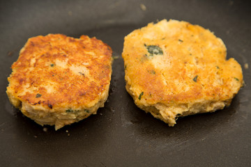 Two Crab Cakes Cooking in Saute Pan