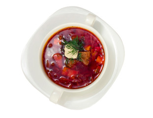 Borsch in white plate isolated on white. Beetroot soup closeup.