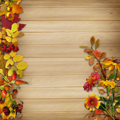 Border and a bouquet of autumn leaves on a wooden background