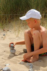 The boy builds the pebbles stack on the sand