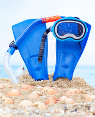 mask, fins and tube in sand background