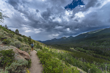 Female hiker on a trail to Bierstadt Lake view of Emerald Mounta