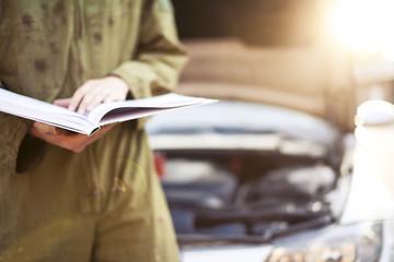 Mechanic reading instructions manual and replacing broken part