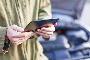 Mechanic using tablet computer wearing overalls under open hood