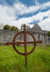 rusty celtic grave cross in front of Muckross Abbey