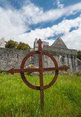 rusty celtic grave cross in front of Muckross Abbey