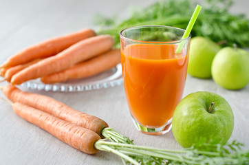 Healthy fresh carrot juice in a glass and green apples