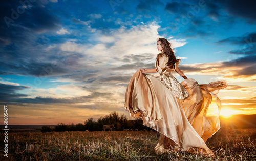 Fashionable beautiful young woman leaving in sunset