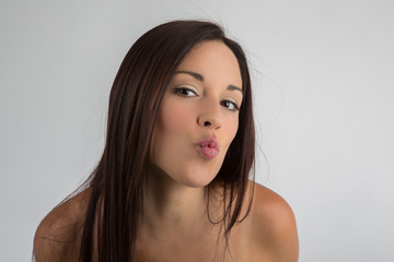 Woman with the mouth closed  expressing a kiss