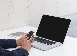 Man hands touching smart phone with laptop computer background
