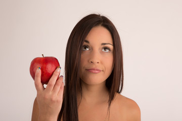 Portrait woman wondering with a red apple , looking up