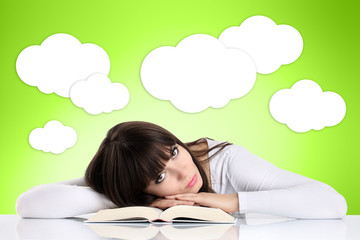 girl reading a book resting on a green background with clouds