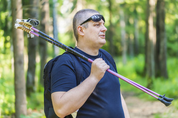 Man with walking sticks on the forest trail
