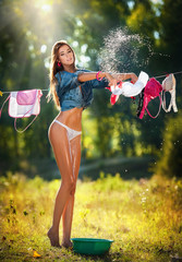 Sexy brunette woman in bikini and shirt  putting clothes to dry