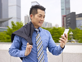 asian business executive looking at cellphone outdoors