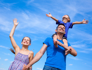 Happy father with kids outdoors against sky