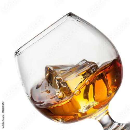 Leinwandbild Motiv Splash of whiskey with ice in glass isolated on white background