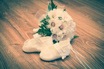 Shoes and bouquet on a wooden floor