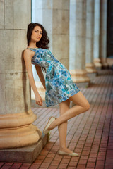 Beautiful young brunette woman standing near column.