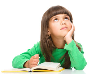 Young girl is daydreaming while reading book