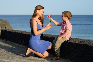 Son gives flowers to his mom