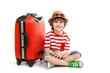 Joyful small boy sits at red suitcase