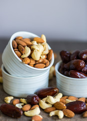 An assortment of healthy nuts in a bowl : almond, cashew, dates