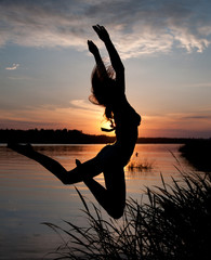 girl in a jump at sunset