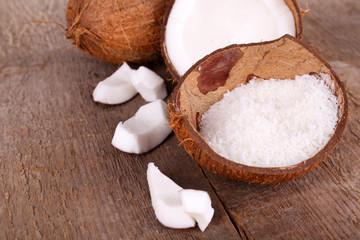 Broken coconut on wooden background
