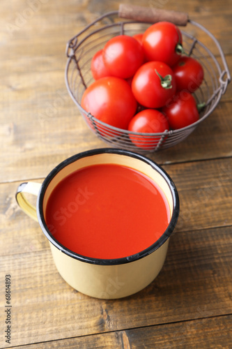 Homemade tomato juice in color mug and fresh tomatoes