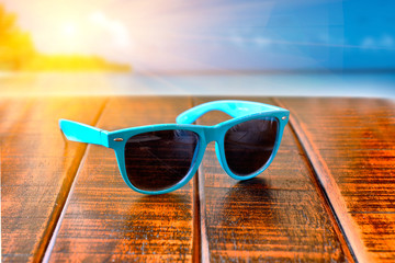 sunglasses on wooden desk at the beach. Summer vacation cincept.