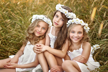Portrait of three young girlfriends with a wreath