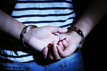 Criminal hands locked in handcuffs on dark background