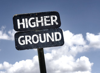 Higher Ground sign with clouds and sky background