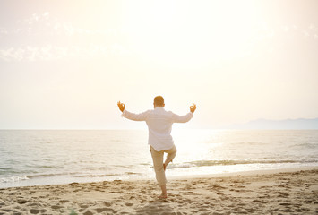 man doing yoga exercises on the beach