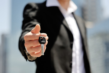 businessman holding a car key in his hand