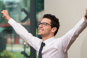 Successful Business Man With Arms Up At The Office