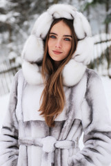 close-up portrait of smiling girl in fur hood in winter city