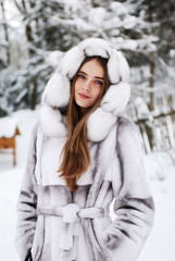 beautiful smiling girl in fur standing in snow winter forest