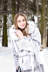 beautiful girl in fur smiling and walking on snow road