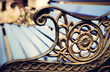 canvas print picture - Detail of old park bench with ornaments, bokeh background