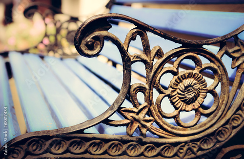canvas print picture Detail of old park bench with ornaments, bokeh background