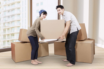 Couple unpacking cardboard in new home 1