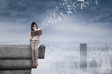 Student reading a book on rooftop 1