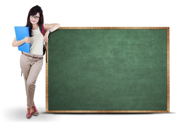 Student standing next to chalkboard