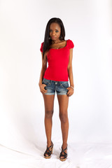black woman in red blouse and shorts, looking serious