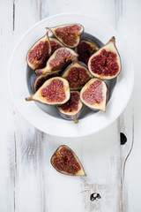 Ripe sliced figs in a glass plate, view from above