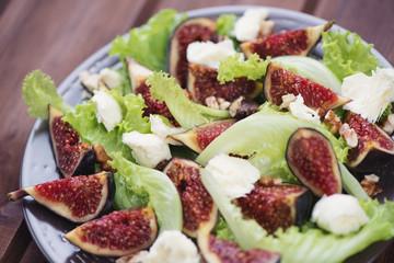 Salad with figs, mozzarella and walnuts, close-up, studio shot